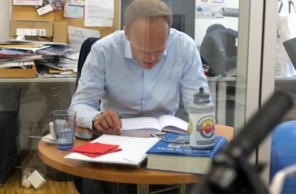 Goldexperte Ronald Stöferle durch die Scheibe fotografiert, mit Runplugged-Trinkflasche ... (16.06.2014)