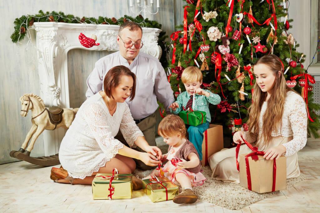 Weihnachten, USA, Bescherung, Geschenke, Heiliger Abend, http://www.shutterstock.com/de/pic-183709607/stock-photo-family-of-five-sits-near-christmas-tree-untying-ribbons-on-gift-boxes.html, © www.shutterstock.com (05.11.2014)